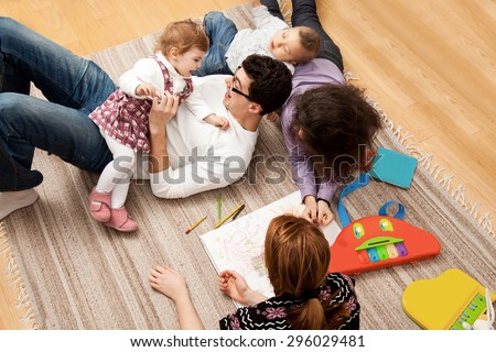 friends or relatives family group of five - two babies and three adults lying on the carpet, dad is tickling his daughter. - stock photo