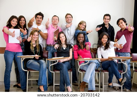 friends or university students smiling in a classroom with thumbs up - stock photo