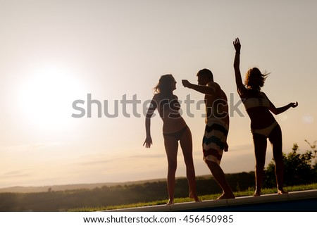Friends partying and enjoying vacation during summer sunset