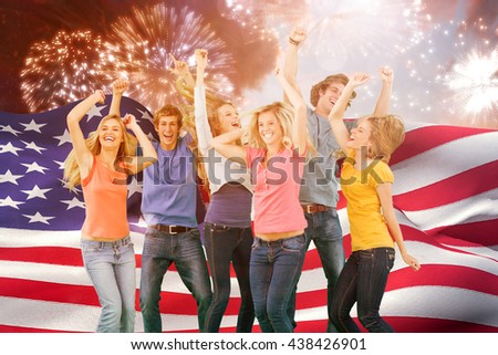 Friends partying together while laughing and smiling against colourful fireworks exploding on black background - stock photo