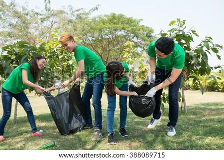 Friends picking up litter in city garden - stock photo