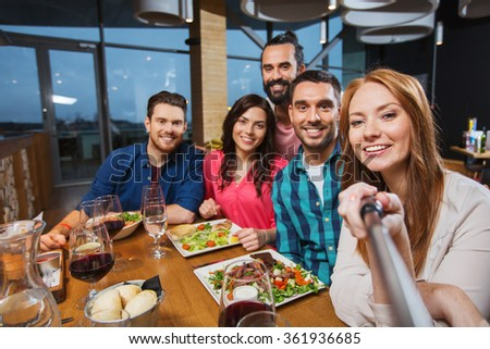friends picturing by selfie stick at restaurant - stock photo