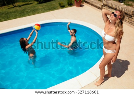 Friends playing ball games in swimming pool