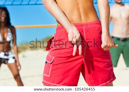 Friends playing beach volleyball, one man giving the strategy to the player in the same team
