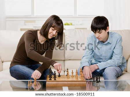 Friends playing chess in livingroom - stock photo
