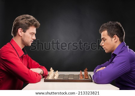 friends playing chess on black background. serious young men thinking about making first move - stock photo