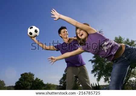 Friends playing football. - stock photo