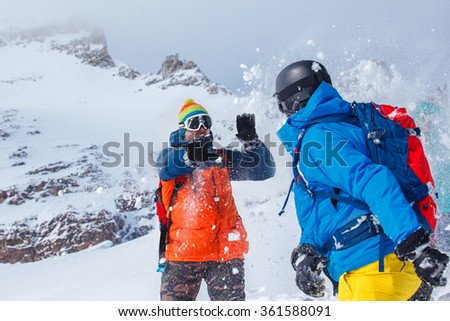 Friends playing snowballs in winter mountains - stock photo