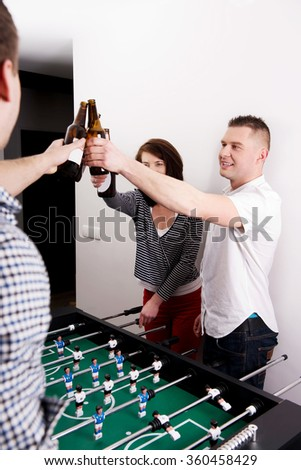 Friends playing table football. - stock photo