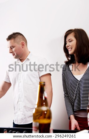 Friends playing table football and drinking beer. - stock photo