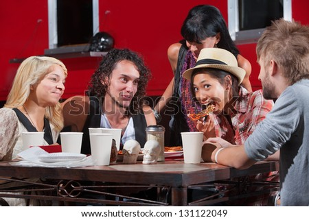 Friends playing with pizza outside at table - stock photo