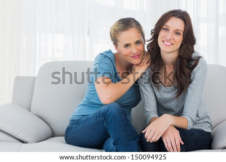 Friends posing while sitting on the couch looking at camera - stock photo