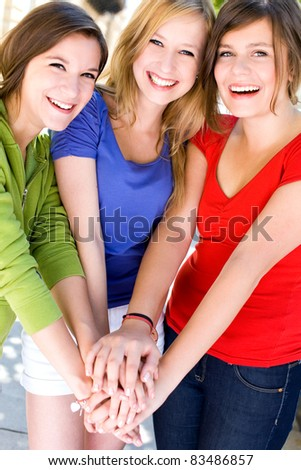 Friends putting hands together - stock photo