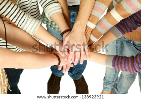 friends putting their hands together in a sign of unity and teamwork - stock photo