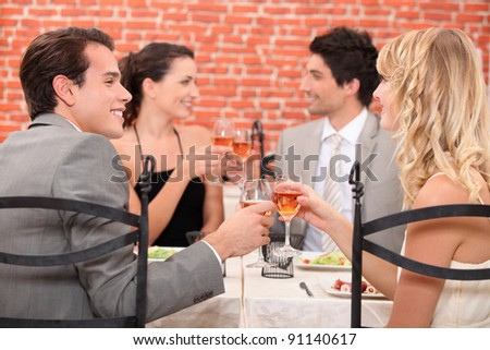 Friends raising their glasses in a toast at a restaurant - stock photo