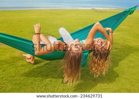 friends relaxing in a hammock  - stock photo