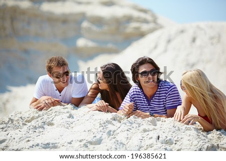 Friends resting on the sand and talking - stock photo