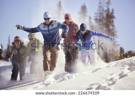 Friends Running Through Snow - stock photo