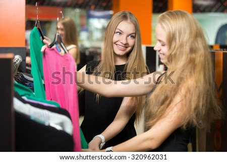 Friends shopping together. Two happy smiling young beautiful women standing in fashion boutique, choosing new clothes, holding hangers with different red and green casual blouses, deciding on color - stock photo