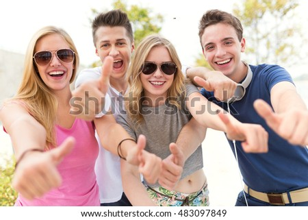 Friends showing thumbs up sign