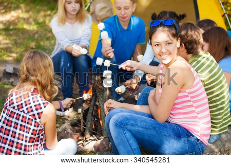 Friends sit on campsite with smores sticks