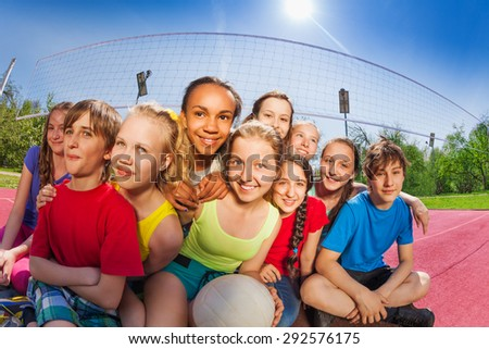 Friends sit on volleyball game court holding ball - stock photo