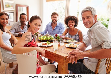 Friends sitting at a dining table, looking at camera - stock photo
