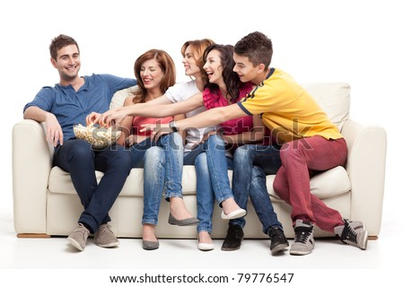 friends sitting on couch reaching for the popcorn bowl - stock photo
