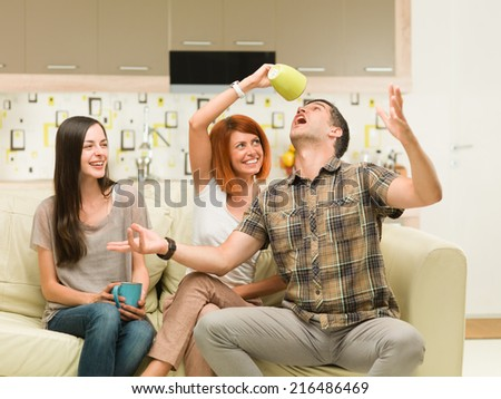 friends sitting on sofa and having fun with coffee mugs - stock photo