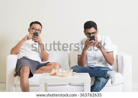 Friends sitting on sofa and playing on their phones at home. - stock photo