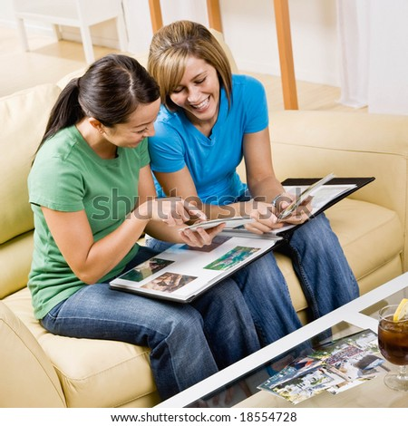 Friends sitting on sofa in livingroom looking at photograph album and remembering happy times - stock photo