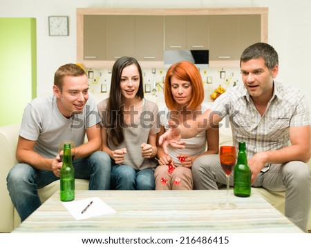 friends sitting on sofa, playing game with dices and having fun - stock photo