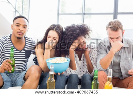 Friends sitting on sofa with a bowl of popcorn in living room - stock photo