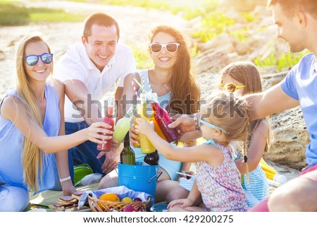 Friends sitting on the sand at the beach at the summer picnic with lemonade
