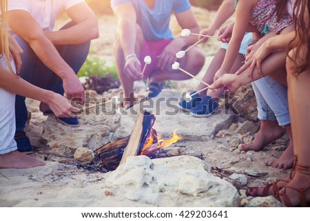 Friends sitting on the sand at the beach in circle with marshmallow on the beach - stock photo