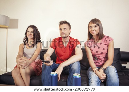 Friends sitting on the sofa watching tv