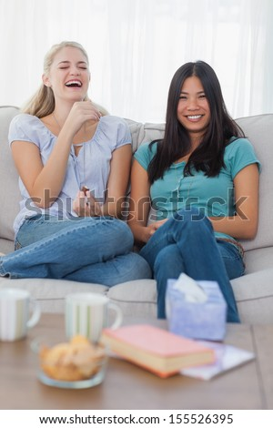 Friends smiling and laughing at home on the couch
