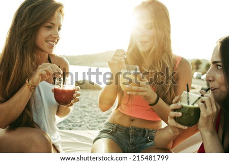 Friends smiling drinking a cocktail - stock photo