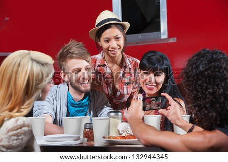 Friends smiling for photos at restaurant - stock photo
