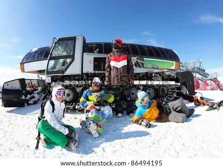 Friends snowboarding on a mountain top about snowcat - stock photo