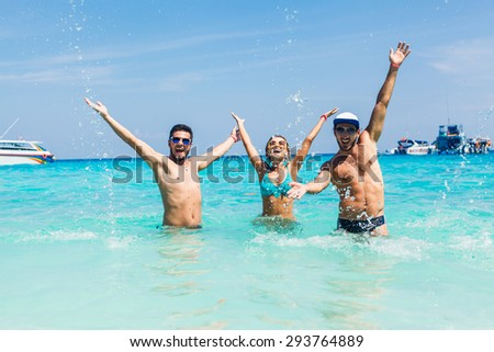 friends standing in bikinis and sunglasses at sea happy hands up in the air victoriously happy