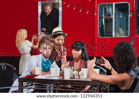 Friends sticking out tongues for photo near food truck - stock photo