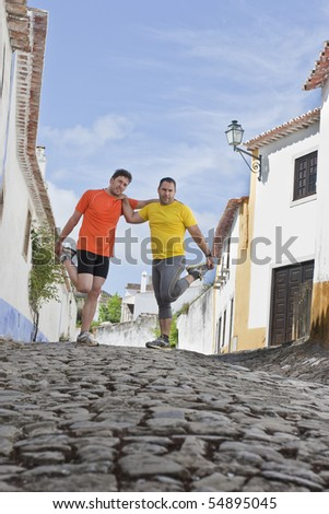Friends stretching to start running on a town road - stock photo