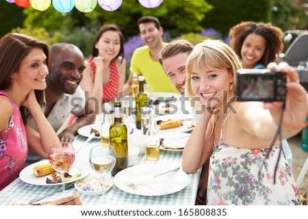 Friends Taking Self Portrait On Camera At Outdoor Barbeque - stock photo