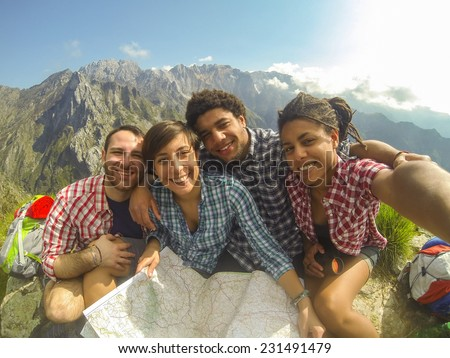 Friends Taking Selfie at Top of Mountain - stock photo