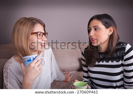 friends talk and drink on a couch - stock photo
