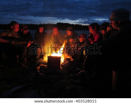 friends tourists sit at a fire and sing songs to the guitar