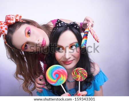Friends. Two girls with creative visage and in bright cloth - stock photo