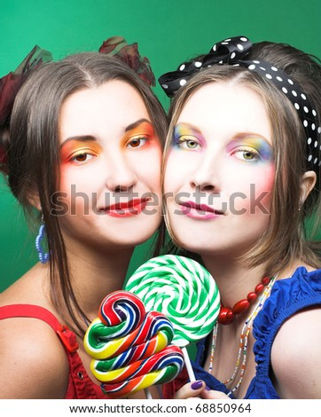 Friends. Two girls with creative visage and with lollipops.