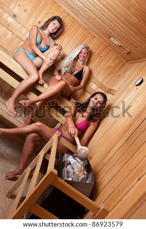 Friends using sauna and making steam - stock photo